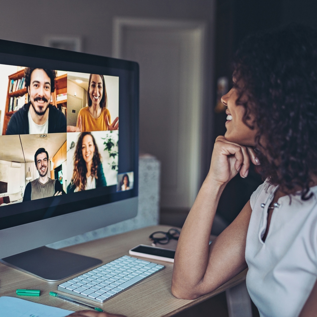 Woman having a video conference with 4 coworkers shown on her screen.